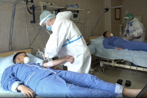 In this file photo made from footage provided by the Russian Defense Ministry on Wednesday, July 15, 2020, medical workers in protective gear prepare to draw blood from volunteers participating in a trial of a coronavirus vaccine at the Budenko Main Military Hospital outside Moscow, Russia. Putin says that a coronavirus vaccine developed in the country has been registered for use and one of his daughters has already been inoculated. Speaking at a government meeting Tuesday, Aug. 11, 2020, Putin said that the vaccine has proven efficient during tests, offering a lasting immunity from the coronavirus. (Russian Defense Ministry Press Service via AP, File)