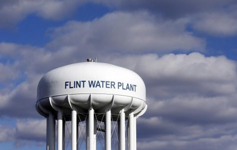 In this March 21, 2016, file photo, the Flint Water Plant water tower is seen in Flint, Mich. Michigan Gov. Gretchen Whitmer says a proposed $600 million deal between the state of Michigan and Flint residents harmed by lead-tainted water is a step toward making amends. Officials announced the settlement Thursday, Aug. 20, 2020, which must be approved by a federal judge. (AP Photo/Carlos Osorio, File)