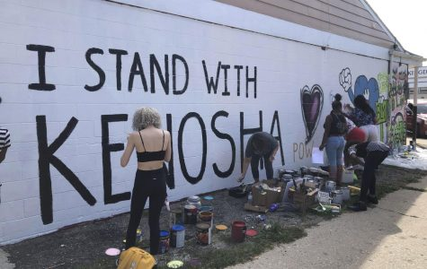 Volunteers paint murals on boarded-up businesses in Kenosha, Wis., on Sunday, Aug. 30, 2020, at an