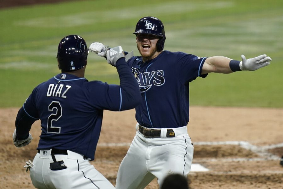 Tampa Bay Rays' Michael Brosseau, right, celebrates with Yandy Diaz after hitting a solo home run during the eighth inning in Game 5 of a baseball American League Division Series against the New York Yankees, Friday, Oct. 9, 2020, in San Diego. (AP Photo/Jae C. Hong)
