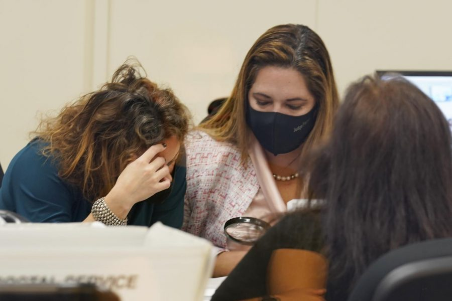Judges Milenia Abreu, left, and Victoria Ferrer examine a vote-by-mail ballot during a canvassing board meeting at the Miami-Dade County Elections Dept., Monday, Nov. 2, 2020 in Doral, Fla. (AP Photo/Marta Lavandier)