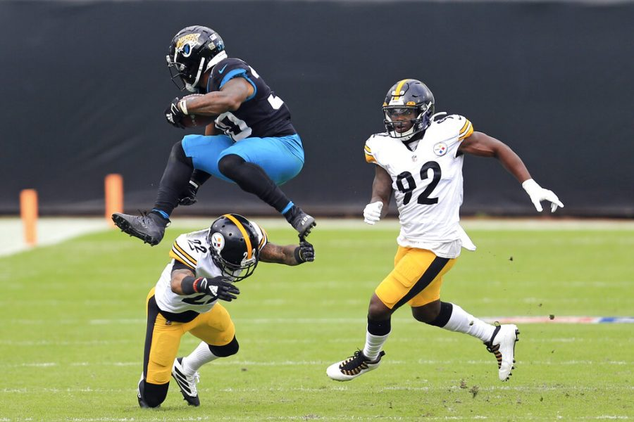 Jacksonville Jaguars running back James Robinson, left, leaps over Pittsburgh Steelers cornerback Steven Nelson (22) as linebacker Olasunkanmi Adeniyi (92) comes in to help during the first half of an NFL football game, Sunday, Nov. 22, 2020, in Jacksonville, Fla. (AP Photo/Matt Stamey)