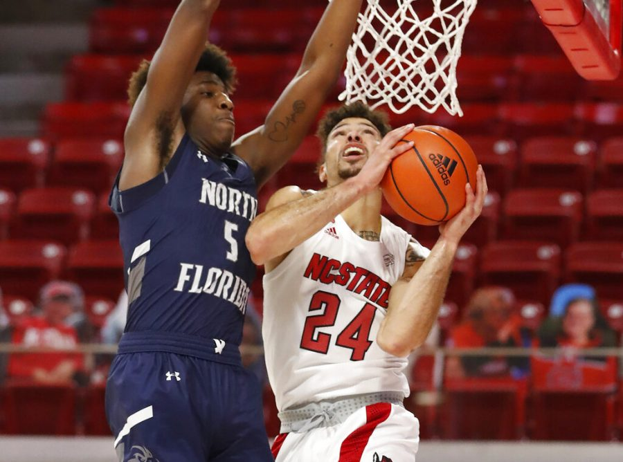 North Carolina State's Devon Daniels (24) shoots as North Florida's Dorian James (5) defends during the first half during the first half of an NCAA college basketball game at Reynolds Coliseum in Raleigh, N.C., Friday, Nov. 27, 2020. (Ethan Hyman/The News & Observer via AP)
