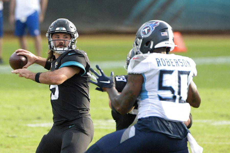 Jacksonville Jaguars quarterback Gardner Minshew II, left, throws a pass over Tennessee Titans linebacker Derick Roberson (50) during the second half of an NFL football game, Sunday, Dec. 13, 2020, in Jacksonville, Fla. (AP Photo/Phelan M. Ebenhack)