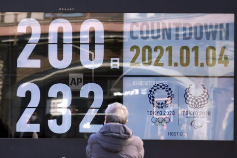 A man looks at a countdown calendar showing 200 day to start Tokyo 2020 Olympics Monday, Jan. 4, 2021, in Tokyo. The countdown clock for the postponed Tokyo Olympics hit 200 days to go on Monday. Also on Monday, Japanese Prime Minister Yoshihide Suga said he would consider calling a state of emergency as new coronavirus cases surge to record numbers in Tokyo and neighboring prefectures.(AP Photo/Eugene Hoshiko)