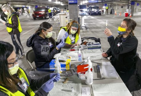 FILE - In this Sunday, Jan. 10, 2021, file photo, Medical professionals from Oregon Health & Science University load syringes with the Moderna COVID-19 vaccine at a drive-thru vaccination clinic in Portland, Ore. The U.S. is entering the second month of the largest vaccination effort in history with a massive expansion of the campaign, opening up football stadiums, major league ballparks, fairgrounds and convention centers to inoculate a larger and more diverse pool of people. (Kristyna Wentz-Graff/Pool Photo via AP, File)