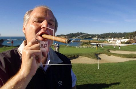 FILE - In this Feb. 3, 2001, file photo, Rush Limbaugh puffs on his Ashton VSG cigar while waiting to tee off from the fifth tee of the Pebble Beach Golf Links during third round play of the AT&T Pebble Beach National Pro-Am in Pebble Beach, Calif. Limbaugh, the talk radio host who became the voice of American conservatism, has died. His death Wednesday, Feb. 17, 2021, at the age of 70 was announced on his website. (AP Photo/Eric Risberg, File)