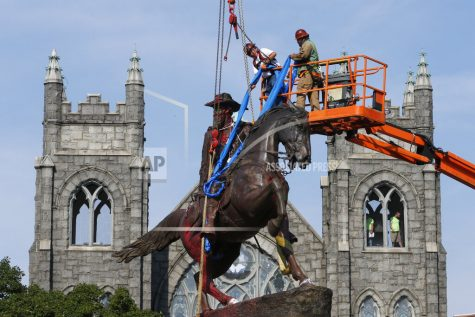 FILE - In this July 7, 2020, file photo, crews attach straps to the statue Confederate General J.E.B. Stuart on Monument Avenue in Richmond, Va. At least 160 Confederate symbols were taken down or moved from public spaces in 2020. That