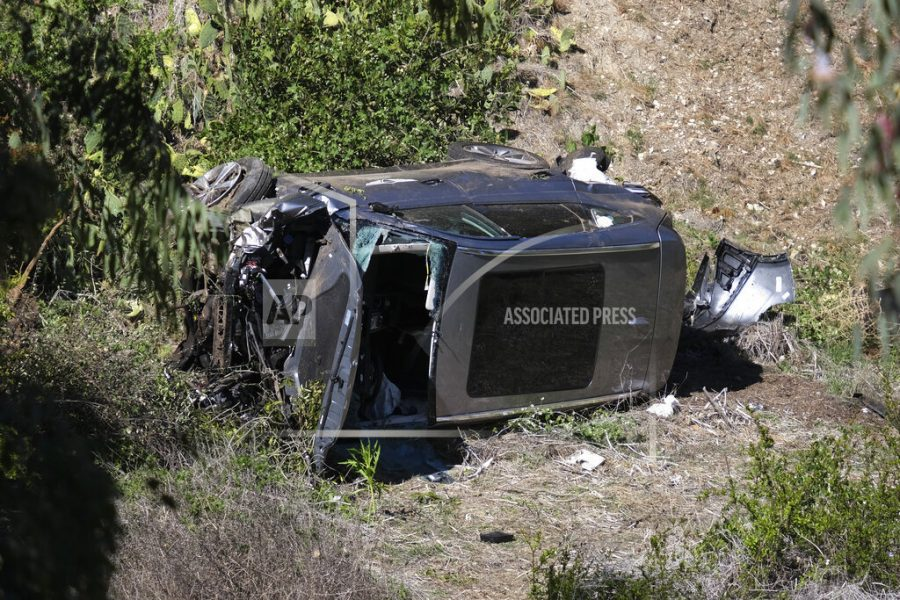 A vehicle rests on its side after a rollover accident involving golfer Tiger Woods along a road in the Rancho Palos Verdes section of Los Angeles on Tuesday, Feb. 23, 2021. Woods suffered leg injuries in the one-car accident and was undergoing surgery, authorities and his manager said. (AP Photo/Ringo H.W. Chiu)