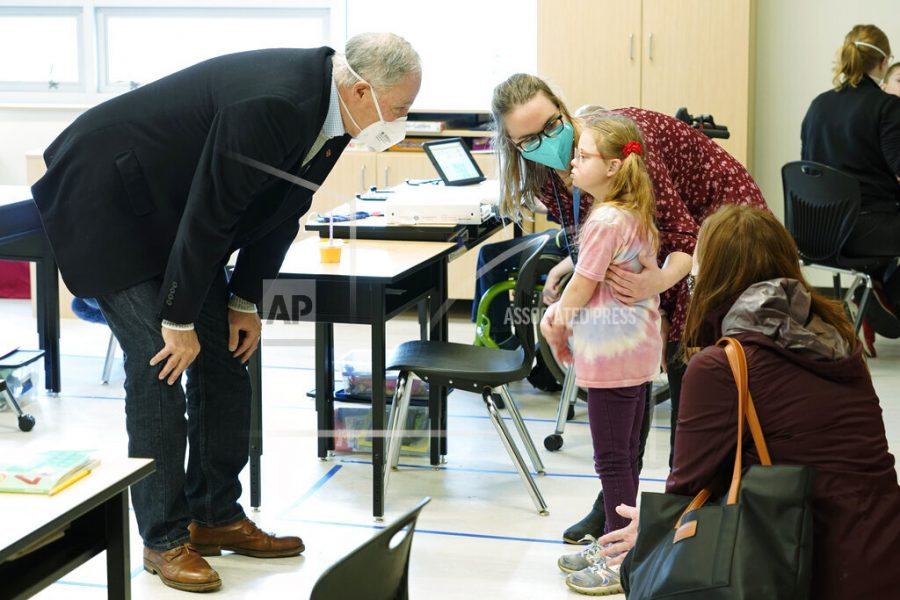 Washington Gov. Jay Inslee, left, talks with a student as teacher Alyson Lykken, center, looks on, Tuesday, Feb. 2, 2021, during a visit to a low-incidence disability classroom at Elk Ridge Elementary School in Buckley, Wash. The school has had some students in classrooms for in-person learning since September of 2020, but other students who attend the school are still learning remotely. Inslee visited the school to observe classrooms and take part in a discussion with teachers and administrators about plans to further open in-person learning in Washington in the future. (AP Photo/Ted S. Warren)