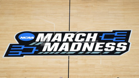 FILE - In this March 20, 2021, file photo the March Madness logo is shown on the court during the first half of a men