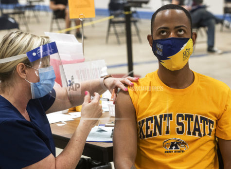 Kent State University student Marz Anderson gets his Johnson & Johnson COVID-19 vaccination from Kent State nurse Beth Krul in Kent, Ohio, Thursday, April 8, 2021. U.S. colleges hoping for a return to normalcy next fall are weighing how far they should go in urging students to get the COVID-19 vaccine, including whether they should — or legally can — require it. (AP Photo/Phil Long)