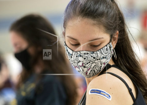 Kent State University student Regan Raeth of Hudson, Ohio, looks at her vaccination bandage as she waits for 15 minutes after her shot in Kent, Ohio, Thursday, April 8, 2021. U.S. colleges hoping for a return to normalcy next fall are weighing how far they should go in urging students to get the COVID-19 vaccine, including whether they should — or legally can — require it. (AP Photo/Phil Long)