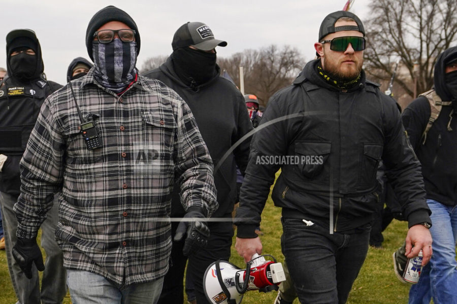 FILE - In this Jan. 6, 2021, file photo, Proud Boys members Joseph Biggs, left, and Ethan Nordean, right with megaphone, walk toward the U.S. Capitol in Washington. A federal judge has ordered Biggs and Nordean, two leaders of the far-right Proud Boys extremist group, to be arrested and jailed while awaiting trial on charges they planned and coordinated an attack on the U.S. Capitol to stop Congress from certifying President Joe Biden's electoral victory. The two had been free since their March 10 indictment, but U.S. District Judge Timothy Kelly concluded April 19, that the two men are dangerous and won