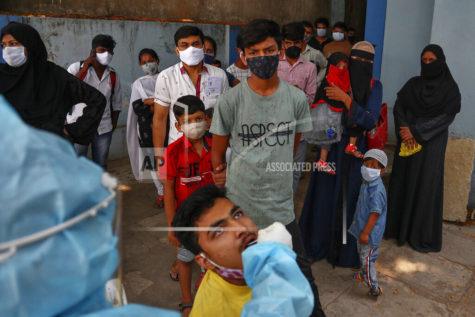 A health worker takes a mouth swab sample of a man to test for COVID-19 as others wait their turn to get tested at a hospital in Hyderabad, India, Monday, April 19, 2021. New infections are rising faster in India than any other place in the world, stunning authorities and capsizing its fragile health system. Overall, India has more than 15.6 million cases, the second-highest after the United States, with 182,553 deaths.(AP Photo/Mahesh Kumar A.)