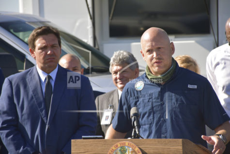 Florida Gov. Ron DeSantis, left, listens as Noah Valenstein, secretary of the Florida Department of Environmental Protection, right, speaks during a news conference at the Piney Point reservoir, Tuesday, April 13, 2021, in Palmetto, Fla. The governor said that Florida will permanently close the leaky Piney Point reservoir that poured millions of gallons of wastewater into Tampa Bay while threatening to burst open and flood nearby homes and businesses. (Ryan Callihan/The Bradenton Herald via AP)