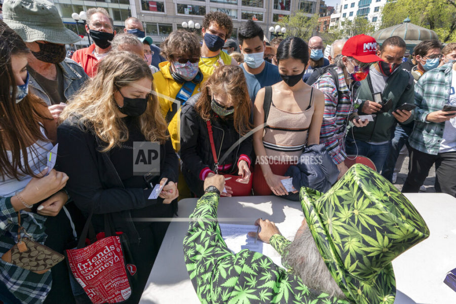 FILE - In this Tuesday, April 20, 2021, file photo, a man wearing a cannabis costume hands out marijuana cigarettes in New York during a