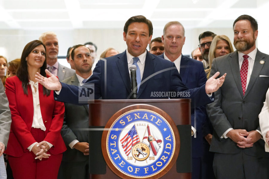 Surrounded by lawmakers, Florida Gov.Ron DeSantis speaks at the end of a legislative session, Friday, April 30, 2021, at the Capitol in Tallahassee, Fla. (AP Photo/Wilfredo Lee)