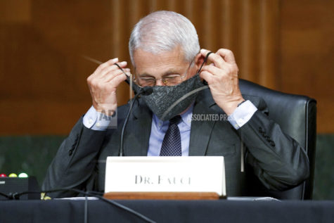 Dr. Anthony Fauci, director of the National Institute of Allergy and Infectious Diseases, puts his face mask back on during a Senate Health, Education, Labor, and Pensions hearing to examine an update from Federal officials on efforts to combat COVID-19, Tuesday, May 11, 2021 on Capitol Hill in Washington. (Jim Lo Scalzo/Pool via AP)