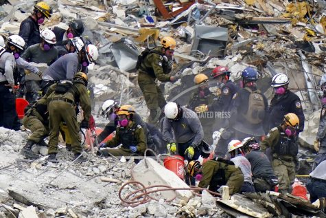 """FILE - Crews from the United States and Israel work in the rubble Champlain Towers South condo, Tuesday, June 29, 2021, in Surfside, Fla.  The Israeli search and rescue team that arrived in South Florida shortly after the Champlain Towers South collapsed last month is heading home after an emotional sendoff in Surfside. The team planned to leave Florida on Sunday, July 11. During a brief Saturday evening ceremony, Miami-Dade Mayor Daniella Levine Cava thanked the battalion for their """"unrelenting dedication. (AP Photo/Lynne Sladky, File)"""