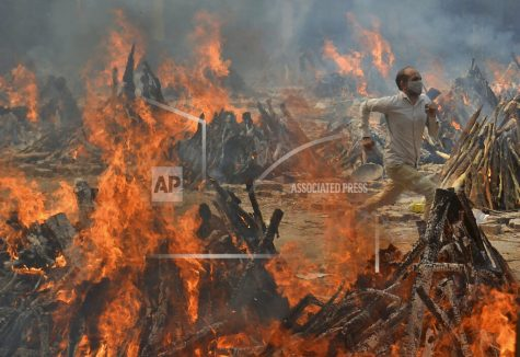 FILE - In this April 29, 2021, file photo, a man runs to escape heat emitting from the multiple funeral pyres of COVID-19 victims at a crematorium in the outskirts of New Delhi, India. India