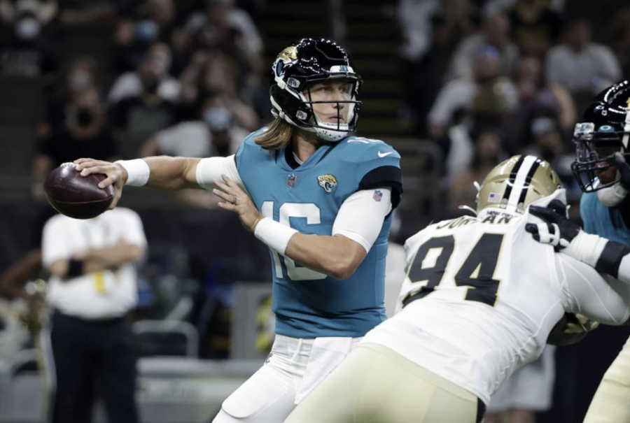 Jacksonville Jaguars quarterback Trevor Lawrence (16) drops back to pass under pressure from New Orleans Saints defensive end Cameron Jordan (94) in the first half of an NFL preseason football game in New Orleans, Monday, Aug. 23, 2021. (AP Photo/Derick Hingle)