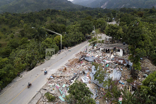 Homes lay in ruins along an earthquake-damaged road in Rampe, Haiti, Wednesday, Aug. 18, 2021, four days after 7.2-magnitude earthquake hit the southwestern part of the country. (AP Photo/Matias Delacroix)