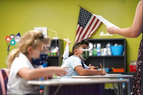 A student listens to the teachers instructions at iPrep Academy on the first day of school, Monday, Aug. 23, 2021, in Miami. Schools in Miami-Dade County opened Monday with a strict mask mandate to guard against coronavirus infections. (AP Photo/Lynne Sladky)