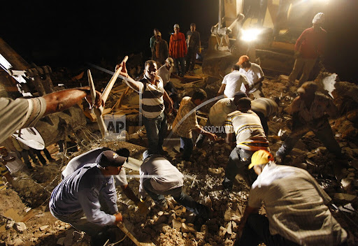 Rescuers work to free trapped survivors and find dead victims in a four story building that collapsed in the 7.0-magnitude earthquake in Port-au-Prince, Haiti, Wednesday, Jan. 13, 2010. (AP Photo/Gerald Herbert)